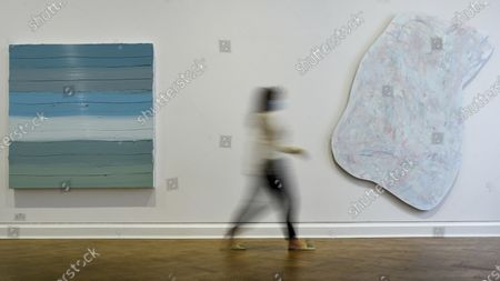 """A staff member wearing a facemask walks between (L) """"Untitled"""", 2019, by Jason Martin and """"Figura Chi"""", 2019, by Imi Knoebel on the opening day of a new exhibition """"Art Basel at Ely House"""" taking place at Galerie Thaddaeus Ropac in Mayfair. The commercial gallery has implemented social distancing guidelines for visitors for its reopening after coronavirus pandemic lockdown restrictions were relaxed by the UK government. The exhibition runs 16 June to 31 July 2020."""
