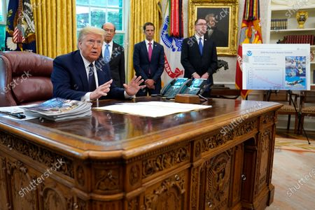 """President Donald Trump speaks as he receives a briefing on the 2020 hurricane season in the Oval Office of the White House in Washington. Watching are Commerce Secretary Wilbur Ross and Neil Jacobs, assistant Secretary of Commerce for Environmental Observation and Prediction, and Pete Gaynor, administrator of the Federal Emergency Management Agency. A report from the National Academy of Public Administration released on Monday, June 15, 2020 says that NOAA's acting chief Jacobs and its then-communications director, Julie Kay Roberts, twice breached the agency's rules designed to protect scientists and their work from political interference, putting out a press statement that """"did not follow NOAA's normal proves and appear to be the result of strong external pressure"""