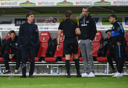 Referee Tobias Stieler of Germany speaks to Bruno Labbadia (L) head coach of Hertha Berlin   and Manager Michael Preetz after a VAR decision during the Bundesliga match between Sport-Club Freiburg and Hertha BSC at Schwarzwald-Stadion in Freiburg im Breisgau, Germany, 16 June 2020.