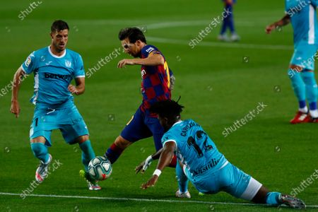 Barcelona's Lionel Messi, center, vies for the ball with Leagnes' Chidozie Awaziem, right, and Leganes' Ruben Perez during the Spanish La Liga soccer match between FC Barcelona and Leganes at the Camp Nou stadium in Barcelona, Spain