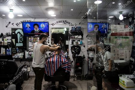Young men in a barber shop listen to the speech of Hezbollah Secretary-General Sayyed Hassan Nasrallah on a TV screen in Beirut, Lebanon, 16 June 2020. Secretary-General of Hezbollah, Sayyed Hassan Nasrallah delivered the speech after the cases of sabotage by demonstrators, who are believed to be motivated to provoke an internal war, and the responsibility to America policy in the region responsible for it due to the economic blockade, in Beirut and Tripoli two days ago,  where he talked about the political situation in Lebanon, and the military conflicts in the Arab countries.  Nasrallah said, whoever presented the martyrs, to save the united of Syria, and does not submit to America and Israel, the 'Caesar' law will not be allowed to defeat it, and its allies who stood with it politically and militarily will not abandon it in the face of the economic war against it.