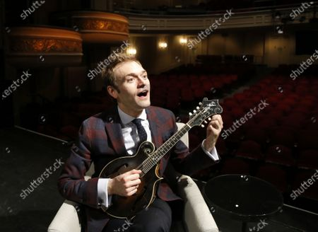 "Chris Thile plays his mandolin on stage at the Fitzgerald Theater in St. Paul, Minn. American Public Media Group has canceled musician Chris Thile's ""Live from Here"" radio show, the successor to Garrison Keillor's ""A Prairie Home Companion."" The media organization announced it was ending national production of Thile's show while cutting 28 staffers at American Public Media and Minnesota Public Radio"