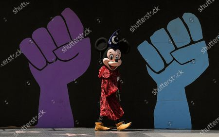 Person dressed as Mickey Mouse walks by a mural that was painted on a boarded-up business on Hollywood Boulevard, in the Hollywood section of Los Angeles