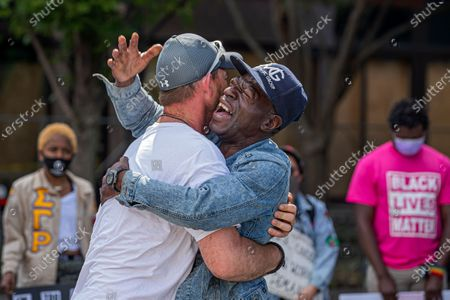 Black Lives Matter demonstrators Tim Higgins (L) and Michael Jone (R) embrace near Centennial Olympic Park in the wake of the Atlanta Police deadly shooting of Rayshard Brooks in Atlanta, Georgia, USA, 16 June 2020. Brooks' death came as the city was already reacting to the death of George Floyd while in the custody of the Minneapolis Police Department.