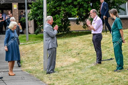 Prince Charles remains socially distanced as he a performs a namaste to Professor Mark Pietroni as he arrives with Camilla Duchess of Cornwall at Gloucestershire Royal Hospital to meet front line key workers who who have responded to the COVID-19 pandemic during a visit to Gloucestershire Royal Hospital.