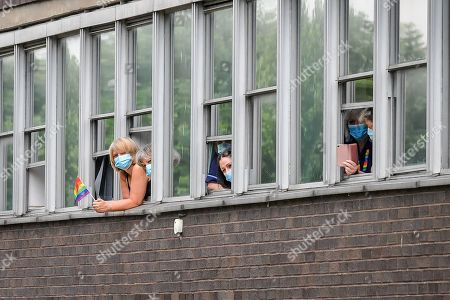 Stock Image of People wear masks as they watch Prince Charles and Camilla Duchess of Cornwall meet other front line key workers who who have responded to the COVID-19 pandemic during a visit to Gloucestershire Royal Hospital.