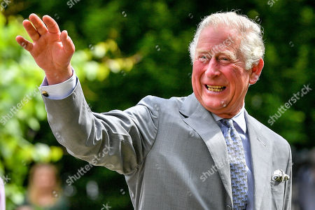 Prince Charles gestures to crowds of hospital staff watching from a distance as he chats with front line key workers who who have responded to the COVID-19 pandemic during a visit to Gloucestershire Royal Hospital.