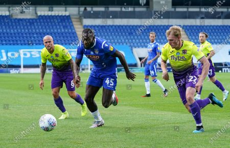 Frank Nouble of Colchester United runs for the ball as Jack Sparkes of Exeter City attempts to challenge