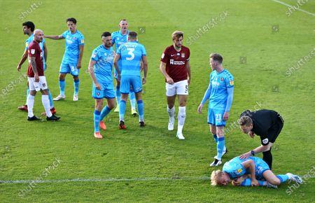 Referee Marc Edwards checks on fouled Ryan Broom of Cheltenham