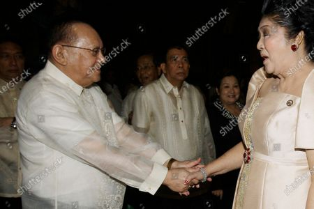 San Miguel Corporation chairman Eduardo Cojuangco Jr., left, greets then congresswoman Imelda Marcos, the widow of the late strongman Ferdinand Marcos, during the 40th wedding anniversary of Philippine Senator Miriam Santiago and Narciso at Manila's Cathedral in Philippines. Philippine tycoon Cojuangco, a key ally of the late dictator Ferdinand Marcos and a low-key businessman who led a food and beverage empire that produced San Miguel beer, has died Tuesday night, June 16, 2020. He was 85