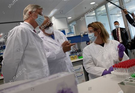Belgium's King Philippe, left, speaks with lab technicians conducting research on coronavirus, COVID-19, at Johnson & Johnson subsidiary, Janssen Pharmaceutical, in Beerse, Belgium, . Janssen Pharmaceutical hopes to begin clinical trials on a potential vaccine for COVID-19 in the middle of the summer