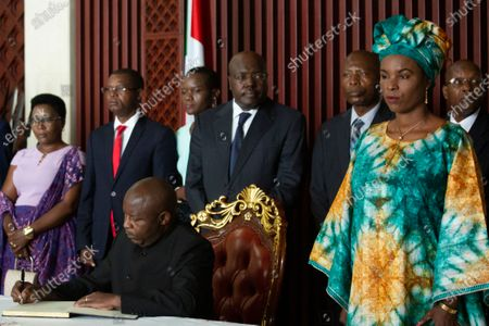 Burundi's president-elect Evariste Ndayishimiye, left, accompanied by his wife Angeline Ndayubaha, right, signs the book of condolences at the presidential palace in Bujumbura, Burundi . Burundi's constitutional court on Friday said president-elect Evariste Ndayishimiye should be sworn in as soon as possible, ending uncertainty created by the death of President Pierre Nkurunziza this week