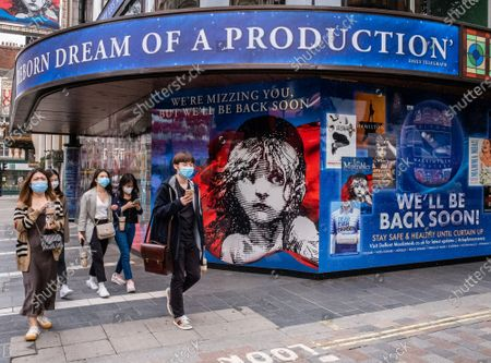"Members of the public in masks walk past Les Miserable in Soho London. Cameron Mackintosh has announced that four of London's best stage musicals will not reopen until 2021. He made the ""heartbreaking"" decision to delay Les Miserable, Mary Poppins, Hamilton and The Phantom of the Opera over social distancing rules."