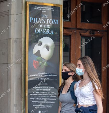 "Two women in a masks walk past Her Majesty's Theatre London. Cameron Mackintosh has announced that four of London's best stage musicals will not reopen until 2021. He made the ""heartbreaking"" decision to delay Les Miserable, Mary Poppins, Hamilton and The Phantom of the Opera over social distancing rules."