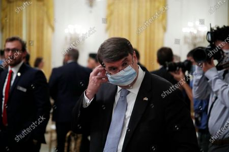 """Veterans Affairs Secretary Robert Wilkie adjusts his mask after an event about the PREVENTS """"President's Roadmap to Empower Veterans and End a National Tragedy of Suicide,"""" task force, in the East Room of the White House, in Washington"""