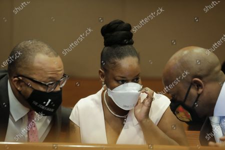 Widow of Rayshard Brooks, Tomika Miller, center, speaks to Chris Stewart, right, and Justin Miller, left, before Fulton County District Attorney Paul L. Howard Jr. speaks at a news conference, in Atlanta. Howard announced former Atlanta Police Officer Garrett Rolfe faces charges including felony murder in the fatal shooting of Rayshard Brooks on June 12