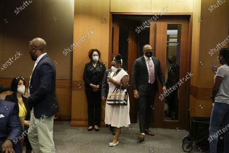 Widow of Rayshard Brooks, Tomika Miller, center, walks into a courtroom with speaks to Chris Stewart, left, and Justin Miller, right, before Fulton County District Attorney Paul L. Howard Jr. speaks at a news conference, in Atlanta. Howard announced former Atlanta Police Officer Garrett Rolfe faces charges including felony murder in the fatal shooting of Rayshard Brooks on June 12