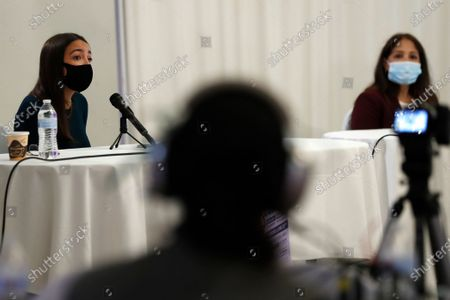 Stock Photo of Technician, center, listens as U.S. Rep. Alexandria Ocasio-Cortez, D, New York, left, speaks while one of her opponents, Badrun Khan, right, listens as the pair faced off in a debate that also included opponent Michelle Caruso-Cabrera, not shown, ahead of New York's June 23 primary, in the Bronx borough of New York