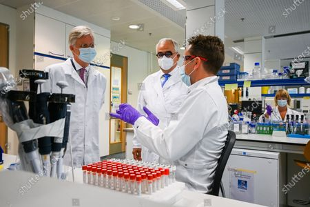 King Philippe (L) and Janssen Pharmaceutica chief scientific officer Paul Stoffels (C) talk to a scientist at work in the laboratroy during a royal visit to the headquarters of Janssen Pharmaceutica in Beerse