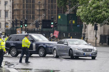 Stock Photo of Security car rear-ends Johnson jag as protester leaps out in front of it. A protester leapt in front of a car carrying Boris Johnson, causing a protection vehicle to crash into it. The dramatic security blunder was captured on camera as the Prime Minister was being driven from the Commons in a convoy. A man protesting about Turkish action against Kurdish rebels ran into the road outside the gates to Parliament, causing Mr Johnson's driver to brake sharply. A Range Rover which was following closely behind, carrying a security team, rammed into the back of the £54,000 Jaguar XJ, leaving a large dent in the boot.