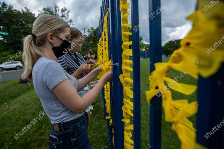 Stock Photo of Northwest Washington's Capital City Public Charter School Spanish teacher Haley Robertson, together with fellow teachers, decorate their school fence with yellow paper spelling out Black Lives Matter, to support their community in response to the recent protests related to the death of George Floyd, who was killed in police custody in Minneapolis on May 25