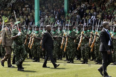 Burundi's President Evariste Ndayishimiye, center, inspects the guard of honor at his inauguration in Gitega, Burundi, . President Evariste Ndayishimiye took power two months early after the abrupt death of his predecessor Pierre Nkurunziza