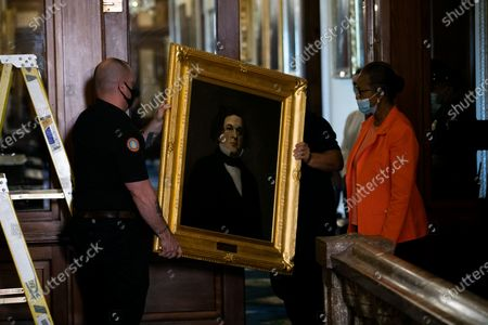 House Clerk Cheryl Johnson looks on as Architect of the Capitol maintenance workers remove a painting of Howell Cobb of Georgia, from the east staircase of the Speakers lobby, on Capitol Hill, in Washington, DC, USA, 18 June 2020. Four portraits of Confederate former Speakers were taken down from the walls of the Capitol.