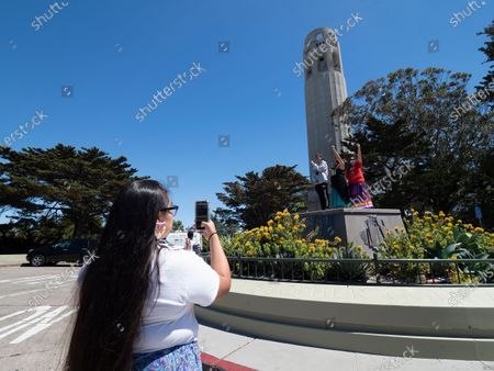 Arianna Antoine-Ramirez (L-R) of the Tohono O'odham Nation Reservation takes a picture of TK Halsey of Lakota, Sharaya Souza of Taos Pueblo and Kiowa, Executive Director of American Indian Cultural District, April McGill of Yuki Wappo, Executive Director of American Indian Cultural Center in San Francisco as they stand on the empty pedestal where a statue of Christopher Columbus once stood next to Coit Tower overlooking the Golden Gate Bridge and the San Francisco Bay in San Francisco, USA, 18 June 2020. San Francisco officials quietly removed the 4,000 pound statue in the early morning. For many Native Americans the statue has always been associated with slavery, subjugation, and conquest.