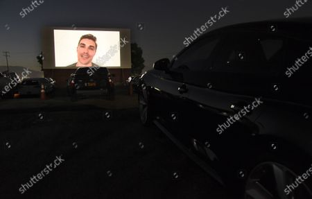 """Dave Franco, director/co-writer of """"The Rental,"""" appears on a movie screen, introducing the film at an advance screening at Vineland Drive-In, in City of Industry, Calif"""