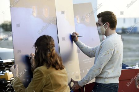 """Dave Franco, right, director/co-writer of """"The Rental,"""" and his wife, cast member Alison Brie, sign posters at an advance screening of the film at Vineland Drive-In, in City of Industry, Calif"""