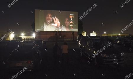 "Dave Franco, left, director/co-writer of ""The Rental,"" and his wife, cast member Alison Brie, are seen on a movie screen as they take part in a Zoom Q&A session from their car following an advance screening of the film at the Vineland Drive-In, in City of Industry, Calif"