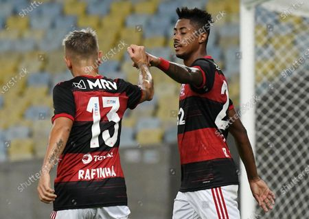Flamengo's Bruno Henrique, left, celebrates with teammate Filipe Luis after scoring during a Rio de Janeiro soccer league match against Bangu at the Maracana stadium in Rio de Janeiro, Brazi,. Rio de Janeiro's soccer league resumed after a three-month hiatus because of the coronavirus pandemic. The match is being played without spectators to curb the spread of COVID-19