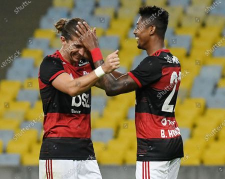 Stock Image of Flamengo's Bruno Henrique, left, celebrates with teammate Filipe Luis after scoring during a Rio de Janeiro soccer league match against Bangu at the Maracana stadium in Rio de Janeiro, Brazi,. Rio de Janeiro's soccer league resumed after a three-month hiatus because of the coronavirus pandemic. The match is being played without spectators to curb the spread of COVID-19