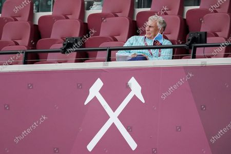 Sir Trevor Brooking hangs his mask on his ear as he watches the game from the West Ham directors box