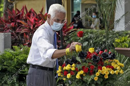 Rep Charlie Crist, D-Fla., places a rose in a vase in honor of black men killed by police officers during a Juneteenth 2020 celebration outside the Dr. Carter G. Woodson African American Museum, in St. Petersburg, Fla. Juneteenth marks the day in 1865 when federal troops arrived in Galveston, Texas to take control of the state and ensure all enslaved people be freed