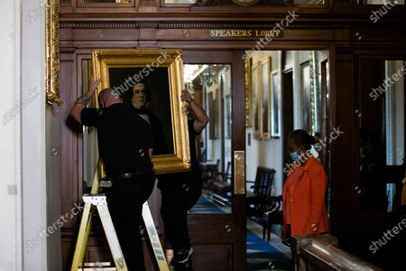 Stock Image of House Clerk Cheryl Johnson looks on as Architect of the Capitol maintenance workers remove a painting of Howell Cobb of Georgia, from the east staircase of the Speakers lobby, in the United States Capitol in Washington, DC,.