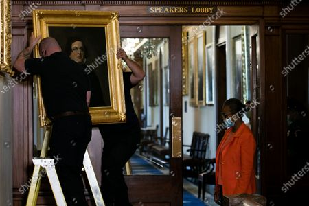 Stock Photo of House Clerk Cheryl Johnson looks on as Architect of the Capitol maintenance workers remove a painting of Howell Cobb of Georgia, from the east staircase of the Speakers lobby, in the United States Capitol in Washington, DC,.