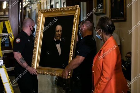 House Clerk Cheryl Johnson looks on as Architect of the Capitol maintenance workers remove a painting of former speaker James Orr of South Carolina, from the east staircase of the Speakers lobby, in the United States Capitol in Washington, DC,.