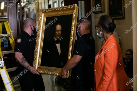 House Clerk Cheryl Johnson looks on as, Architect of the Capitol maintenance workers remove a painting of former speaker James Orr of South Carolina, from the east staircase of the Speakers lobby, in the United States Capitol in Washington, DC,.