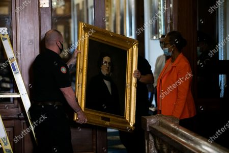 House Clerk Cheryl Johnson looks on as Architect of the Capitol maintenance workers remove a painting of Howell Cobb of Georgia, from the east staircase of the Speakers lobby, in the United States Capitol in Washington, DC,.
