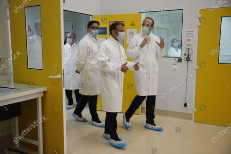 French President Emmanuel Macron talks with Thomas Triomphe, Executive Vice President of Sanofi Pasteur, next to Paul Hudson, Chief Executive Officer of Sanofi, as he visits an industrial development laboratory at the French drugmaker's vaccine unit Sanofi Pasteur plant in Marcy-l'Etoile, near Lyon, France, June 16, 2020.