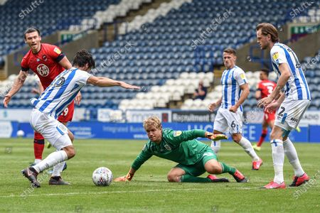 Goalkeeper Jonas Lossl (49) of Huddersfield Town scrabbles onto a ball loose in the penalty box.