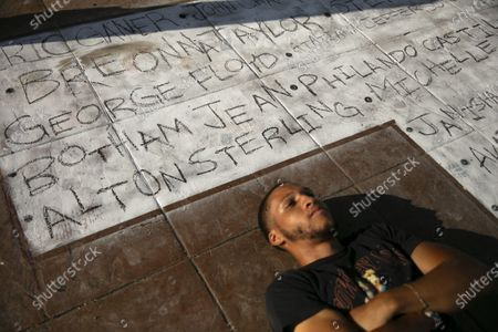 Kyle Johnson poses for a drone with a chalk mural bearing names of people killed by police, during a Juneteenth celebration in Los Angeles, . Juneteenth is the holiday celebrating the day in 1865 that enslaved Black people in Galveston, Texas, learned they had been freed from bondage, more than two years after the Emancipation Proclamation