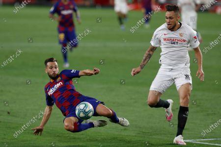 Barcelona's Jordi Alva, left, duels for the ball with Sevilla's Lucas Ocampos during the Spanish La Liga soccer match between Sevilla and FC Barcelona at the Ramon Sanchez-Pizjuan stadium in Seville, Spain