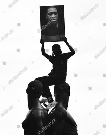 Stock Picture of A protestor sits atop a statue holding a picture of George Floyd near Grand Army Plaza as part of a celebration of Juneteenth in New York City.