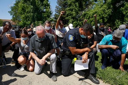 Stock Image of Sacramento Mayor Darrell Steinberg, foreground left, and Sacramento Police Chief Daniel Hahn, foreground right, kneel with others for a moment of silence at a rally in honor of George Floyd, in Sacramento, Calif. Black police chiefs representing departments from across California, called for changing state law so they can immediately fire officers for egregious behavior, with due process appeals only after the fact