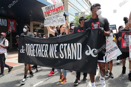 Stock Picture of Players of the NBA Washington Wizards and WNBA Washington Mystics led by John Wall and Bradley Beal and Natasha Cloud of the Mystics down the streets of DC to the MLK Memorial