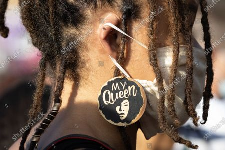 A woman wears a face mask and earrings depicting American activist and academic Angela Davis with the phrase 'My Queen' during a Juneteenth holiday celebration in Los Angeles, California, USA, 19 June 2020. Juneteenth - a portmanteau between the month of June and the word 'nineteenth' - marks the day when the last enslaved people in the US were emancipated in 1865 in Galveston, Texas, more then two years after the Emancipation Proclamation of 1863.