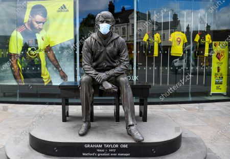 A statue of the former Watford Manager Graham Taylor with the protective mask seen outside the stadium before the English Premier League soccer match between Watford FC and Leicester City in Watford, Britain, 20 June 2020.