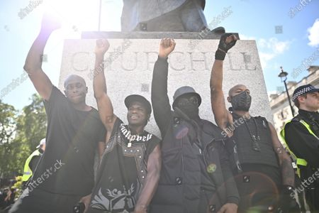 Protesters raise a fist underneath a statue of Sir Winston Churchill as Black Lives Matter demonstrators gather in Parliament Square, central London. Strict restrictions have been placed on demonstrations by Black Lives Matter , who have called for the removal of statues from throughout the UK of historical characters involved in the slave trade.